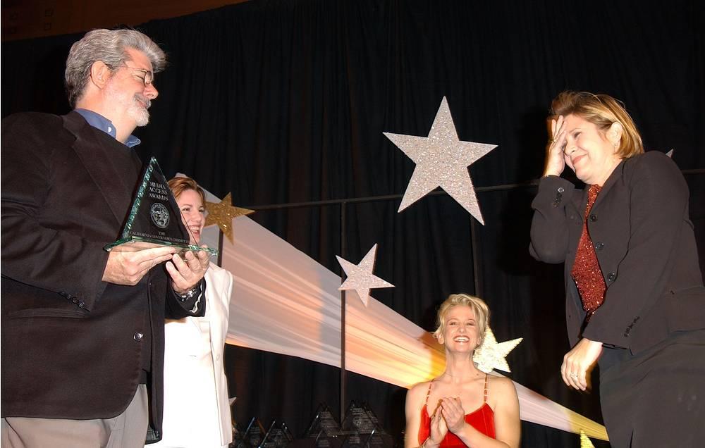 Режиссер Джордж Лукас вручает премию Гильдии киноактеров Кэрри Фишер на 20 ежегодной премии Media Access. Гостиница Sheraton, Лос-Анджелес, 2 ноября 2002 года