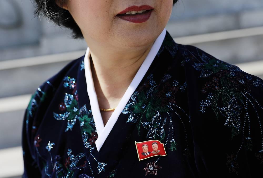 Гид по Пхеньяну в традиционном корейском костюме, на который приколот значок с изображением Ким Ир Сена и Ким Чен Ира. С недавнего времени на значках начал появляться и третий Ким — нынешний правитель страны Ким Чен Ын