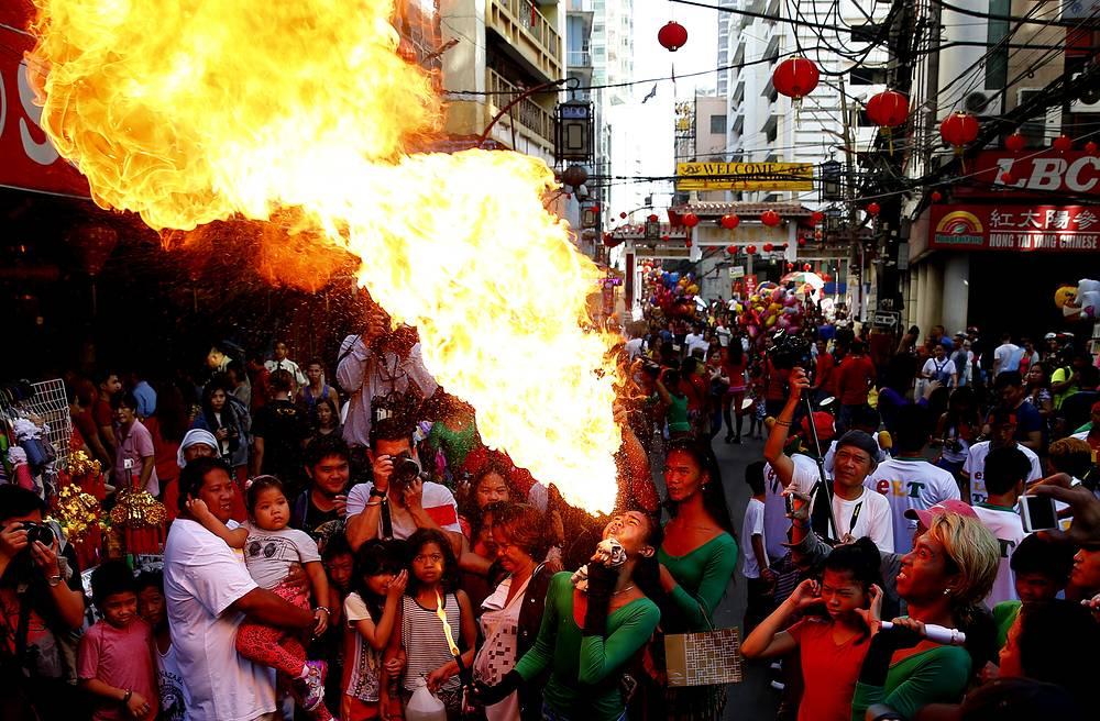 Огнеглотатель выступает на праздновании китайского Нового года в китайском квартаре Манилы, Филиппины