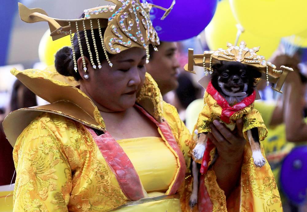 Женщина с собакой, символом наступившего года, на праздничной церемонии в Маниле, Филиппины
