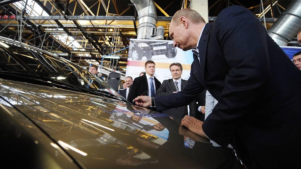 Владимир Путин расписывается на капоте машины