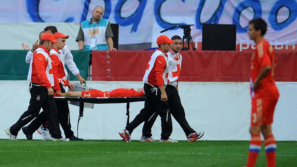 Медицинские работники уносят с поля игрока сборной России Александра Анюкова