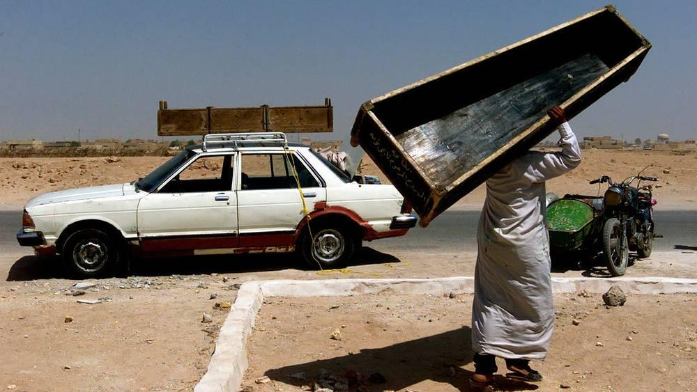 Жоао Сильва / The New York Times. Мужчина идет по улице после похорон матери и дочери, которые погибли во время взрыва в городе Ан-Наджаф, Ирак, 2003 г.
