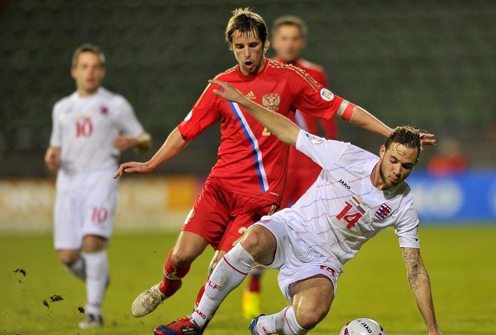 Игрок сборной России Дмитрий Комбаров в борьбе с соперником