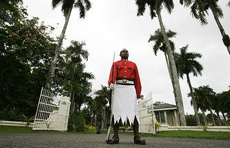 A ceremonial guard backed by an armed Fijian soldier at the entrance to Fiji's Government House in the capitol Suva