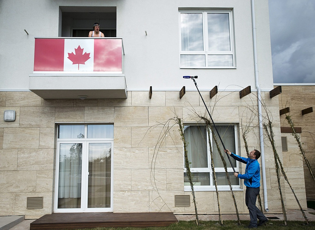 Canadian speed skater Mathieu Giroux trains on a bicycle on his room's balcony as a Russian media person tries to ask a question