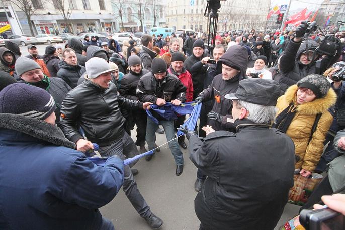 The crowd rips apart a European Union flag
