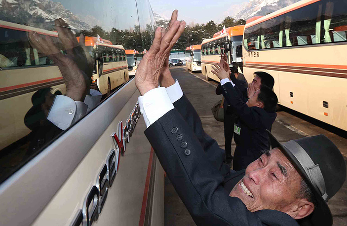 North Korean man, waves to his South Korean relatives in a bus after a separated family reunion meeting