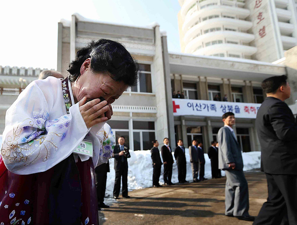A North Korean woman sobs as she leaves her South Korean older brother