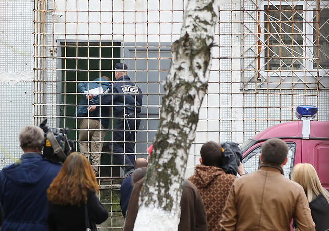 People watch a policeman convoy a detained man near the district court in Kharkiv