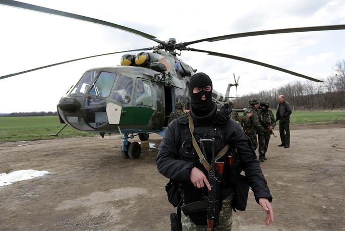 Ukrainian soldiers near a military helicopter, near Izyum city in Kharkiv Region