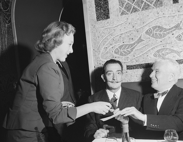 Salvador Dali and Charlie Chaplin gice autographs while having dinner, 1954