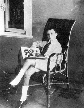 Vladimir Nabokov reading a book on butterflies in Vyra estate in 1907