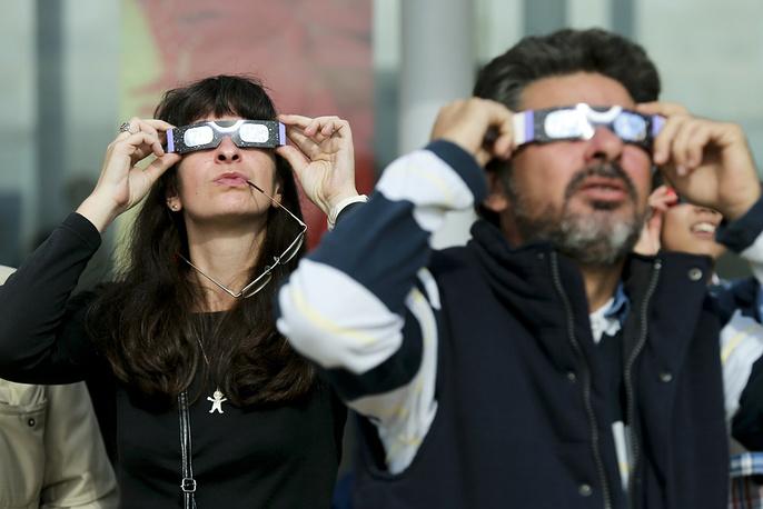 People observe a solar eclipse in Estoril, Portugal in 2013