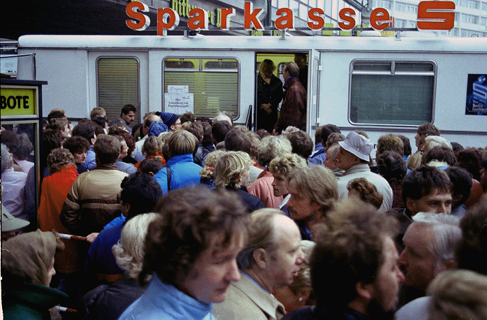 "East German citizens crowd a mobile bank office in West Berlin to pick up ""welcome money"" donated by the West Germany government for East Germans visiting the West"