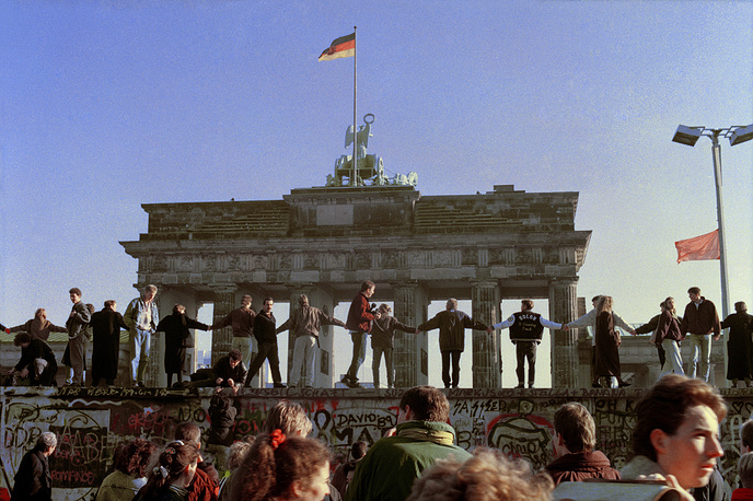 Berliners sing and dance on top of The Berlin Wall to celebrate the opening of East-West German borders