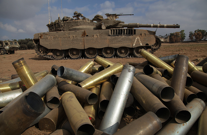 Empty shells next an Israeli Merkava tank