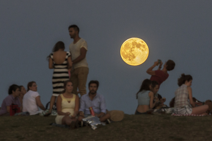 People gather in the park as a supermoon rises in Madrid