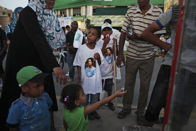 Children wearing T-shirts with the portrait of former Libyan leader Muammar Gaddafi