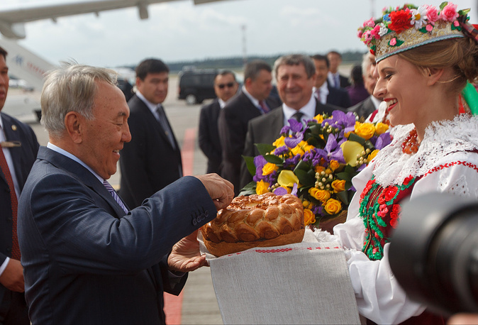 Kazakhstan's President Nursultan Nazarbayev gets traditional salt and bread upon arrival in Minsk