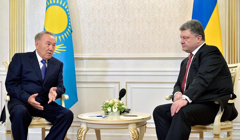 Kazkahstan's President Nursultan Nazarbayev (L) talks to Ukrainian President Petro Poroshenko