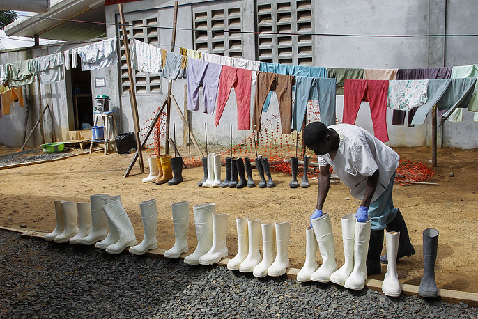 Photo: A Liberian nurse picking up boots after being disinfected at the ELWA Ebola Treatment Unit in Monrovia, Liberia, 04 October 2014