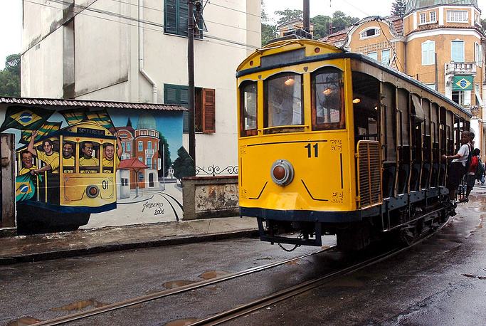 Photo: a tram passes a mural showing Brazil's national soccer team in the Rio de Janeiro
