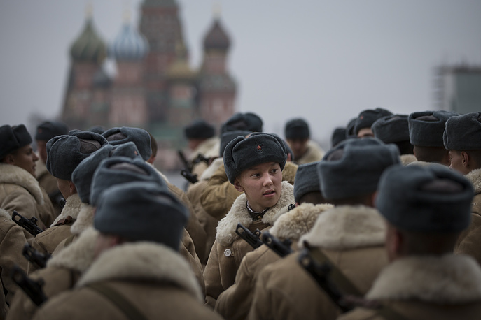Photo: Russian soldiers dressed in Red Army World War II uniforms in front of a backdrop of St. Basil Cathedral in Moscow