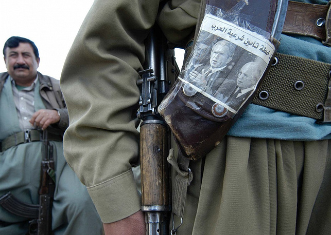 Photo: A Kurdish soldier shows his decorated clipholder for his Kalashnikov machine gun, Northern Iraqi town of Kifry, 2003