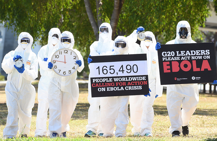 Photo: Protesters with posters and clocks to repersesent time running out during an Ebola protest event in Brisbane, Australlia 15 November 2014