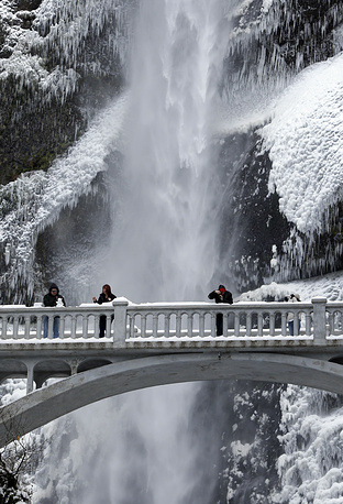 Photo: Vistors play with snow and take photos against the backdrop of ice and snow covered walls at Multnomah Falls in the Columbia River Gorge, Oregon,  November 14, 2014