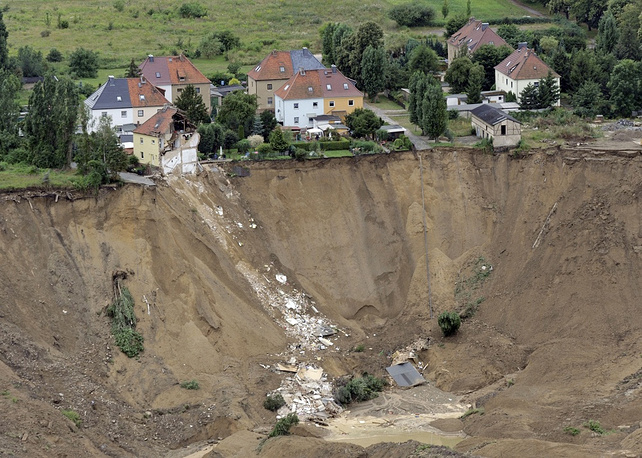 Ruined house and a destroyed street in Nachterstedt, Germany, 2009 Collapse happened after an old open-cast coal mine converted to a lake