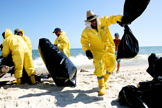 BP and the US Department of Justice agreed to a record-setting $4.525 billion in fines. Photo: Clean-up workers tossing trash bags full of oil spill refuse on a Gulf Shores beach, Alabama, USA