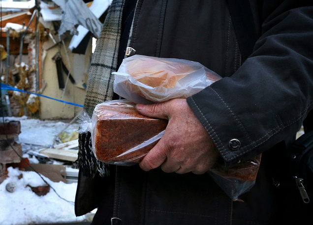 Photo: Man walks with bread past the badly damaged marketplace near Donetsk's railway station