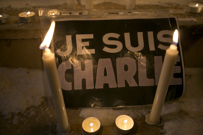"Candles are lit near a sign that read in French ""I am Charlie"" in Kosovo capital Pristina"