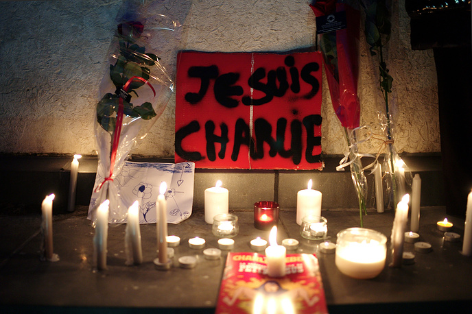 """A banner reading """"I am Charlie"""" is displayed with candles during a gathering to pay respect for the victims of a terror attack against a satirical newspaper, in Paris, France"""