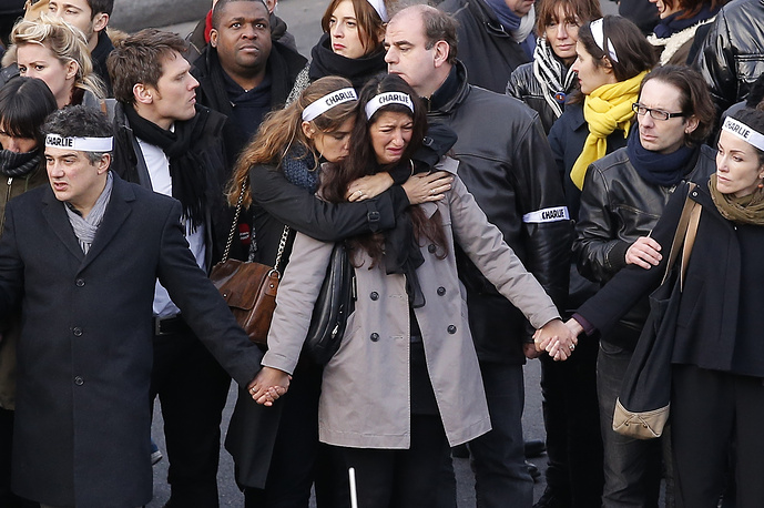 The march was led by relatives of the journalists of the satirical magazine Charlie Hebdo, police officers and shoppers at a kosher supermarket killed by terrorists. Photo: Families and relatives walk and hold banners reading 'Charlie' during a march to honor victims of the terrorist attacks in Paris