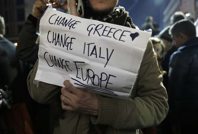 Photo: A supporter of left-wing Syriza party holding a placard after exit poll results in Athens