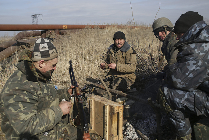 Photo: Ukrainian servicemen cleaning their weapon at the checkpoint near Luhanske village not far of Debaltsevo, Donetsk area
