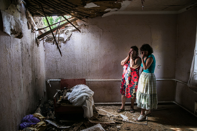 Local residents cry inside their house destroyed during a Ukrainian forces night shelling, Donetsk region, May 2014