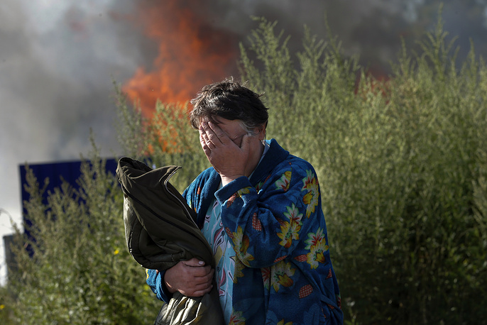 A woman near her burning house after shelling in the city of Slovyansk, Donetsk region, June 2014