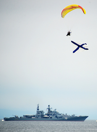 A paratrooper with Russian Naval flag over the Sovremenny class destroyer Bystry during Navy Day parade in Vladivostok