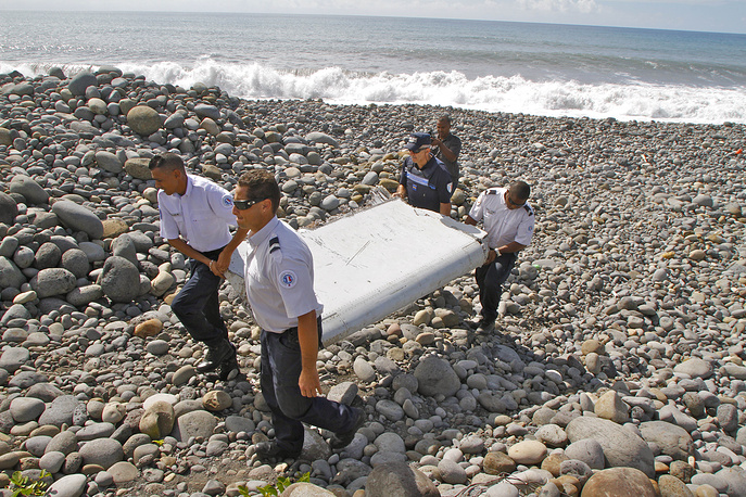 """Police officers looking at a piece of debris from a plane in Saint-Andre, Reunion. Air safety investigators, one of them a Boeing investigator, have identified the component as a """"flaperon"""" from the trailing edge of a Boeing 777 wing. Flight 370, which disappeared March 8, 2014 is the only 777 known to be missing"""