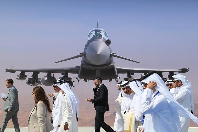 Visitors walking past a wall banner at the 2015 Dubai Airshow