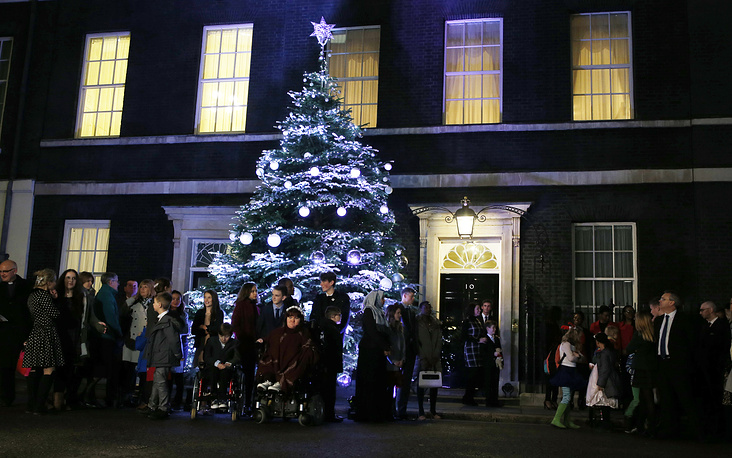 Guests gathering with Britain's Prime Minster David Cameron by the traditional 10 Downing Street Christmas tree in London, UK