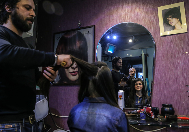 A girl has her hair done at a hairdresser's in Salah al-Din, Aleppo