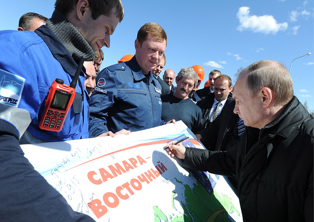 Vladimir Putin signing an autograph on a placard as he talks to Vostochny Cosmodrome workers after the launch