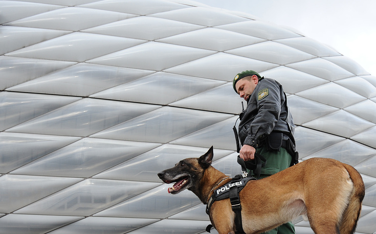 A police officer with his dog standing in front of the stadium prior to the soccer match in Munich, Germany