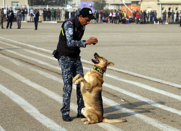 An Iraqi policeman and his dog demonstrating their skills during a ceremony marking Police Day at the police academy in Baghdad, Iraq