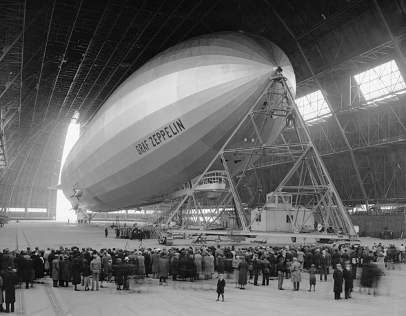 The first lighter-than-air aircraft to circumnavigate under its own power was the rigid airship LZ 127 Graf Zeppelin in 1929. Photo: Sightseers watch as Graf Zeppelin is refueled in hanger, 1933